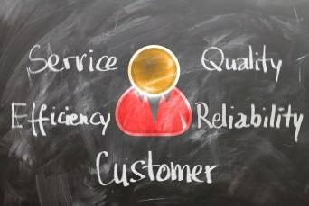 """Words """"customer, service, efficiency, quality"""" and """"reliability"""" written on a blackboard"""