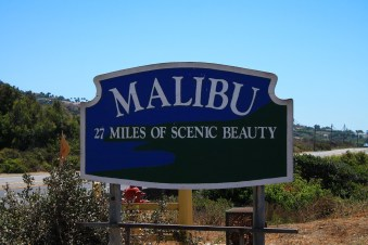 """""""Malibu, 27 miles of scenic beauty"""" written on a big board, plants and a clear sky in the background - one of the most elite LA neighborhoods"""