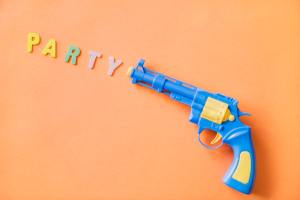 "A toy gun shooting letters that spell the word ""party"""
