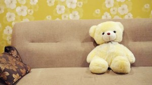 Teddy bear and a cushion on a sofa