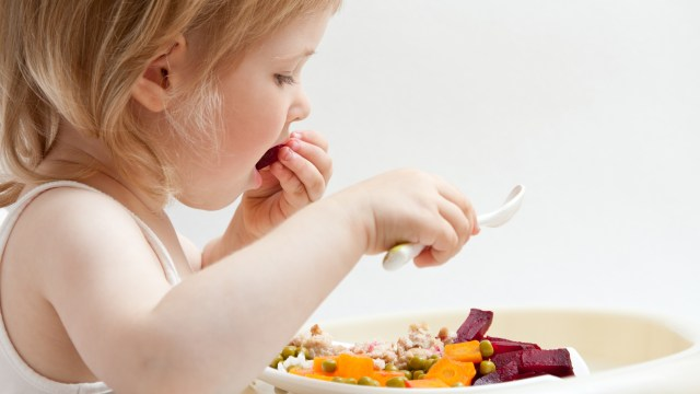 Adorable baby girl eating fresh vegetables