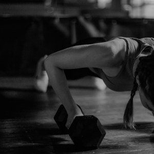 woman doing pushups while holding dumbbells