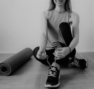 woman in workout clothes tying shoe