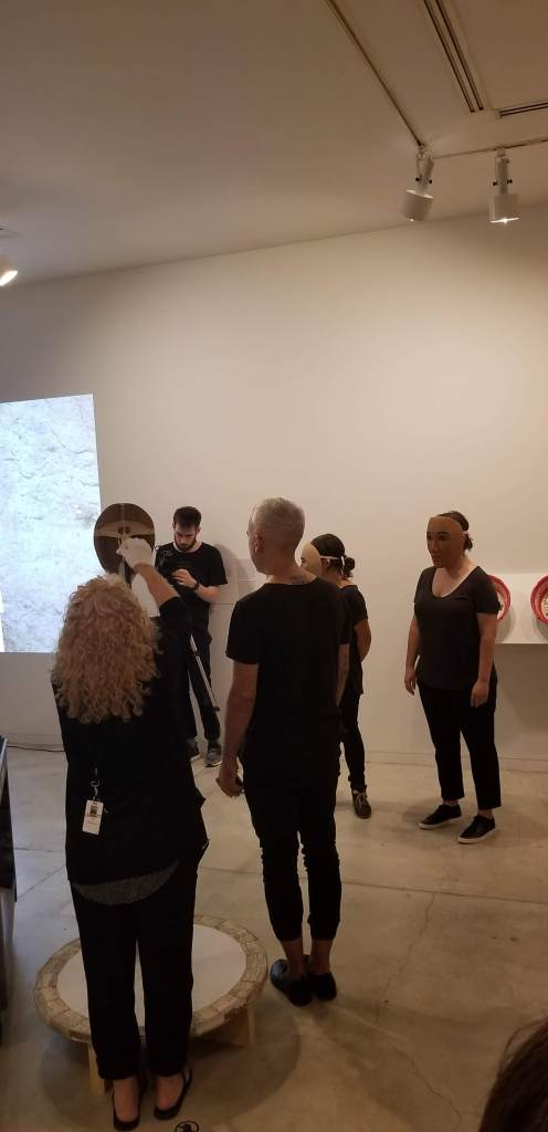 Three portrait masks carved by Haida artist Corey Bulpitt is removed from the display and activated by artists Ayumi Goto, Peter Morin and senior curatorial fellow Tarah Hogue.
