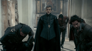 Cardinal Richelieu stands, shocked, amidst Porthos, Aramis and d'Artagnan, who are all bowing to someone offscreen.