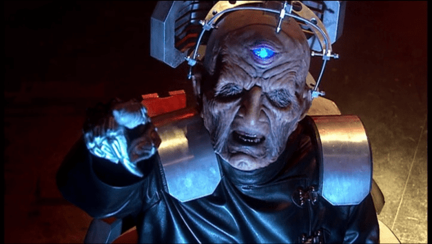 Davros, a hideous, eyeless half-dalek creature, points a metal hand upwards.
