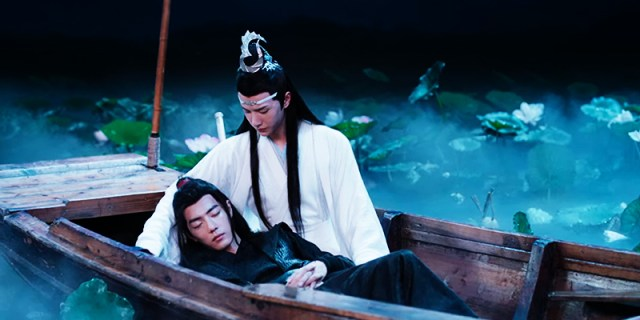 Wei Wuxian, a man in black robes, lying in the arms of Lan Wangji, a man in white robes and wearing an ornate hair decoration