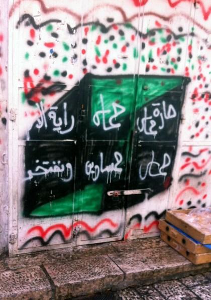 """בהיעדר יכולת לכנס עצרות, חמאס מבליטה את נוכחותה בפרהסיה של העיר בכתובות קיר. בתמונה: כתובת של חמאס בשכונת באב א-זהרה: """"שכונת חמאס. חמאס היא דגל האִסלאם ואנו גאים בה."""" (צילום: פנחס ענברי)"""