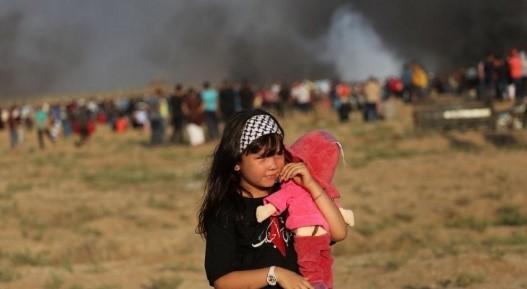 תצלום מבויים מאתר יורו-פאל. ילדה עם סרט פלסטיני מחזיקה בובה. צעדות השיבה ככלי גיוס אהדה אירופית לעזה.