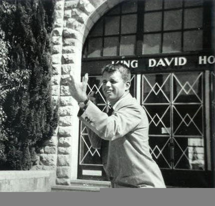 Kennedy outside of the King David Hotel striking a military pose.