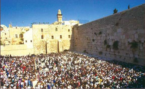 Praying at the Western Wall, 1995. After the Mughrabi Quarter was evacuated, the narrow Western Wall alley was widened into a large plaza that accommodated tens of thousands of Jewish worshippers. (Moshe Milner, Government Press Office)
