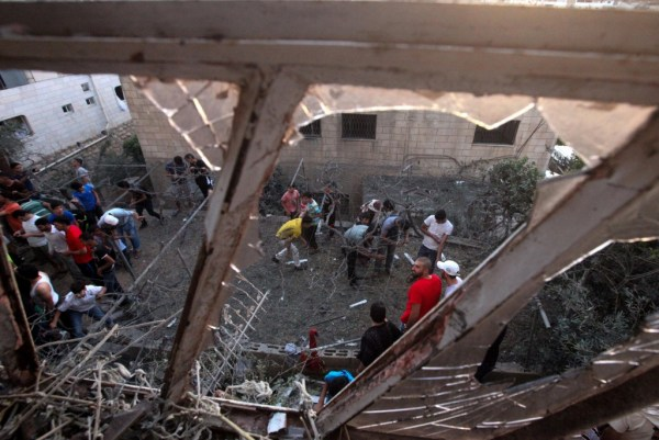 Palestinians in the West Bank city of Hebron inspect the damage to a house that was hit by a rocket fired from the Gaza Strip on July 12, 2014. (EPA/Abed Al Hashlamoun)