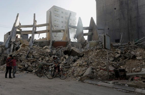 Palestinians walk next to the rubble of the 15-story Basha Tower that collapsed from Israeli airstrikes in Gaza City on August 26, 2014. All tenants were evacuated before the strike. (AP/Adel Hana)
