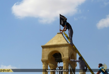 Replacing cross atop Mosul church with ISIS flag. (Source: ISIS)