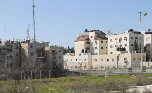 "One facing the other after the separation fence was built in Jerusalem: roofs of the Arab neighborhood of A-Ram with the black water tanks face the roofs of the Jewish neighborhood of Neve Yaakov with the white water tanks. Tens of thousands of Arabs moved to the ""Israeli side"" of the fence after it was built. The process will probably intensify if the fence and the border are extended within the city and Jerusalem is divided. (Photograph: Ariel Shragai)"