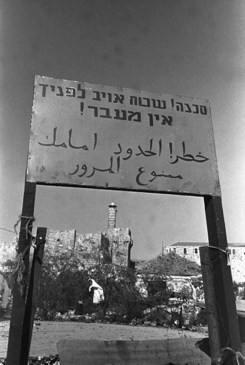 """From 1948 to 1967 the city, before being unified, was divided by walls, wire fences, and signs like this one, which says """"Danger! Enemy Territory Ahead! No Entry!"""" In the picture: a view from west Jerusalem into east Jerusalem, July 1951. (Government Press Office)"""