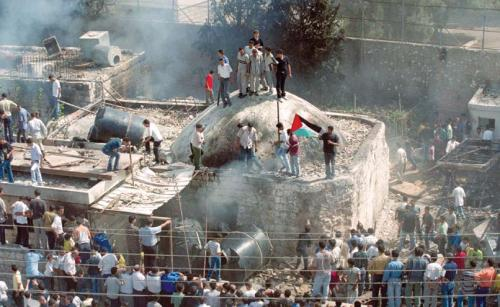 "Palestinians stand on the roof of Joseph's Tomb in Nablus on October 7, 2000, after Palestinian fighters and civilians had stormed the Israeli enclave, destroyed holy books, and set the sacred site on fire in a victory ""celebration"" held a few hours after the IDF evacuated the site. (AP photo/Lefteris Pitarkis)"