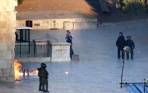 Israeli security forces stand guard at one of the main entrances of the al-Aqsa mosque as Palestinians throw firebombs from inside the mosque. (AFP)