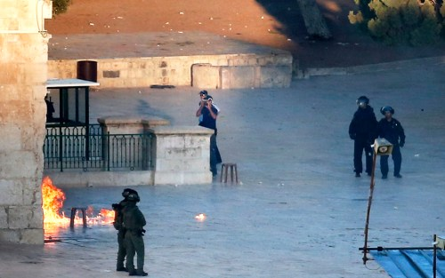 Israeli security forces stand guard at one of the main entrances of the al-Aqsa mosqueas Palestinians throw firebombs from inside the mosque. (AFP)