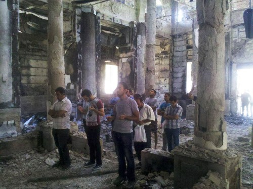 Coptic Christians praying in a burned church