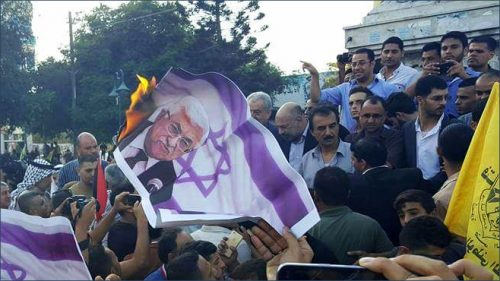 Dahlan supporters burning pictures of Abbas during a demonstration in Gaza