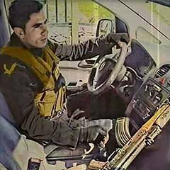 Palestinian Forces policeman, Muhammad Turkman, with his AK-47 assault rifle