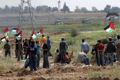 Palestinian demonstrators with their flags along the border fence with Israel.