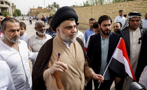 Iraqi Shiite leader Moqtada al-Sadr shows his ink-stained index finger and holds a national flag outside a polling station in Najaf on May 12, 2018.