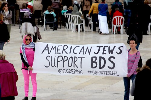 Two Jewish members of Code Pink next to the Western Wall in Jerusalem with banner supporting BDS