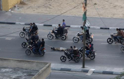 Hamas gunmen drag the body of a suspected collaborator