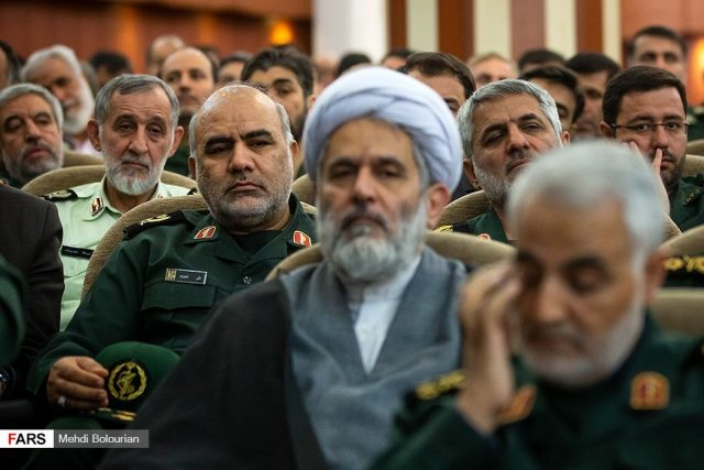 Ali Nasiri (sitting behind the cleric and commander Hossein Taib and not far from Gen. Qasem Soleimani)