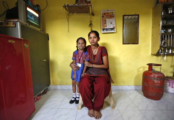 (Via the Atlantic) India: Sulochna Mohan Sawant, 23, with her five-year-old daughter Shamika Sawant inside their home in Mumbai, on February 13, 2014. Sulochna, who works as a maid, wanted to become a doctor when she was a child. However, she could only study until the age of 14. Sulochna wants her daughter to become a teacher, Shamika also wants to become a teacher. (Reuters/Mansi Thapliyal)