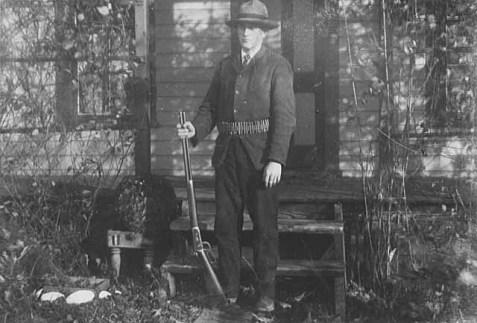 Man standing with gun and ammunition belt