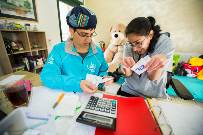 JDC volunteer uses a calculator to assist a young Israeli woman with disabilities to organize her finances.