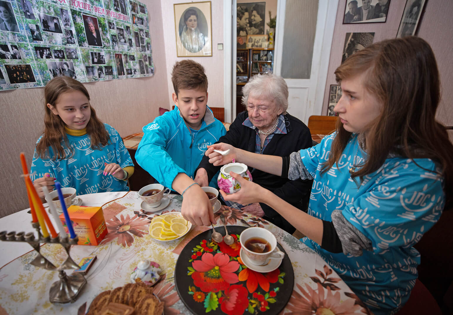 Three young JDC volunteers in the former Soviet Union make tea with an elderly female client during Channukah.