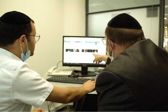 Two Israeli men in yarmulkes sit in front of a computer, while one of them points at the screen.