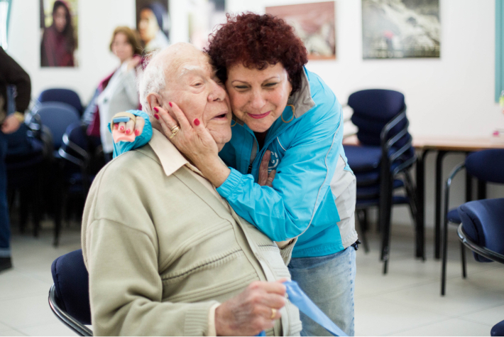 JDC volunteer embraces elderly male client in Israel.