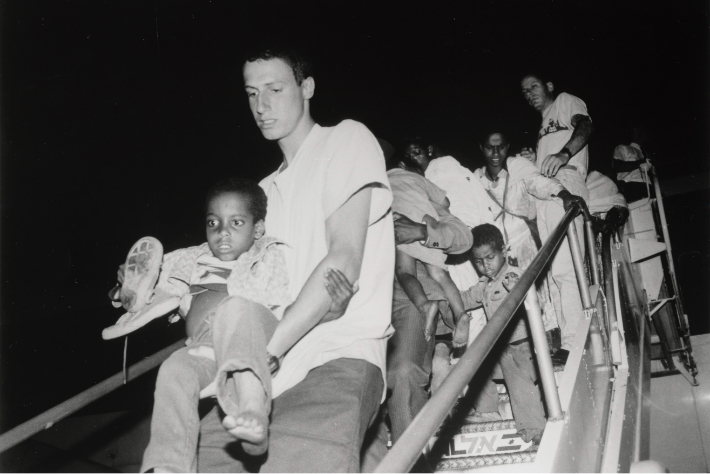 A JDC volunteer carrying an Ethiopian-Jewish boy down from a flight during Operation Solomon.