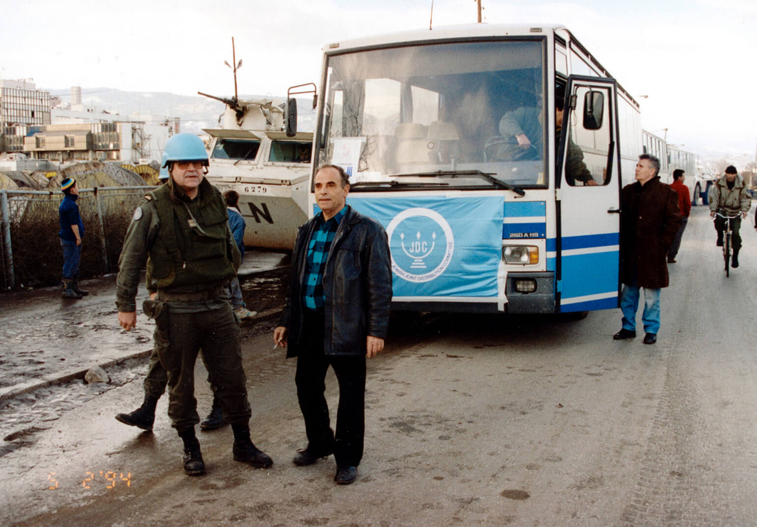JDC aid workers standing next to a bus and military tank in Sarajevo during the Siege of Sarajevo.