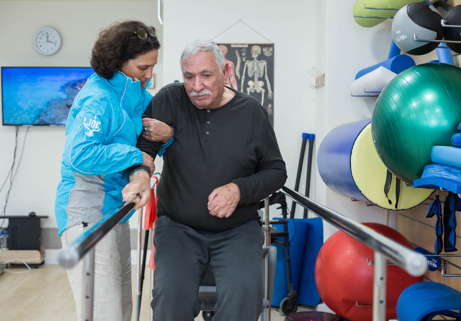 A JDC worker in Israel rehabilitates an elderly man by helping him to walk.