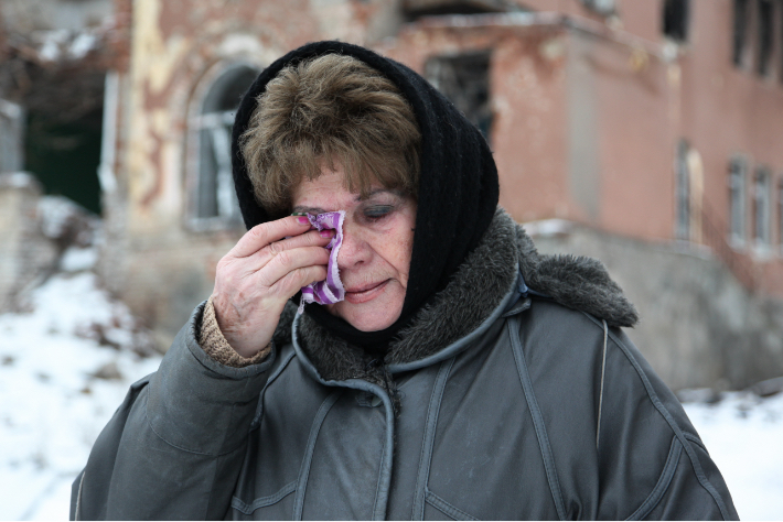 A Jewish woman in a winter coat dabbing her eye in Eastern Ukraine while it's snowing outside.