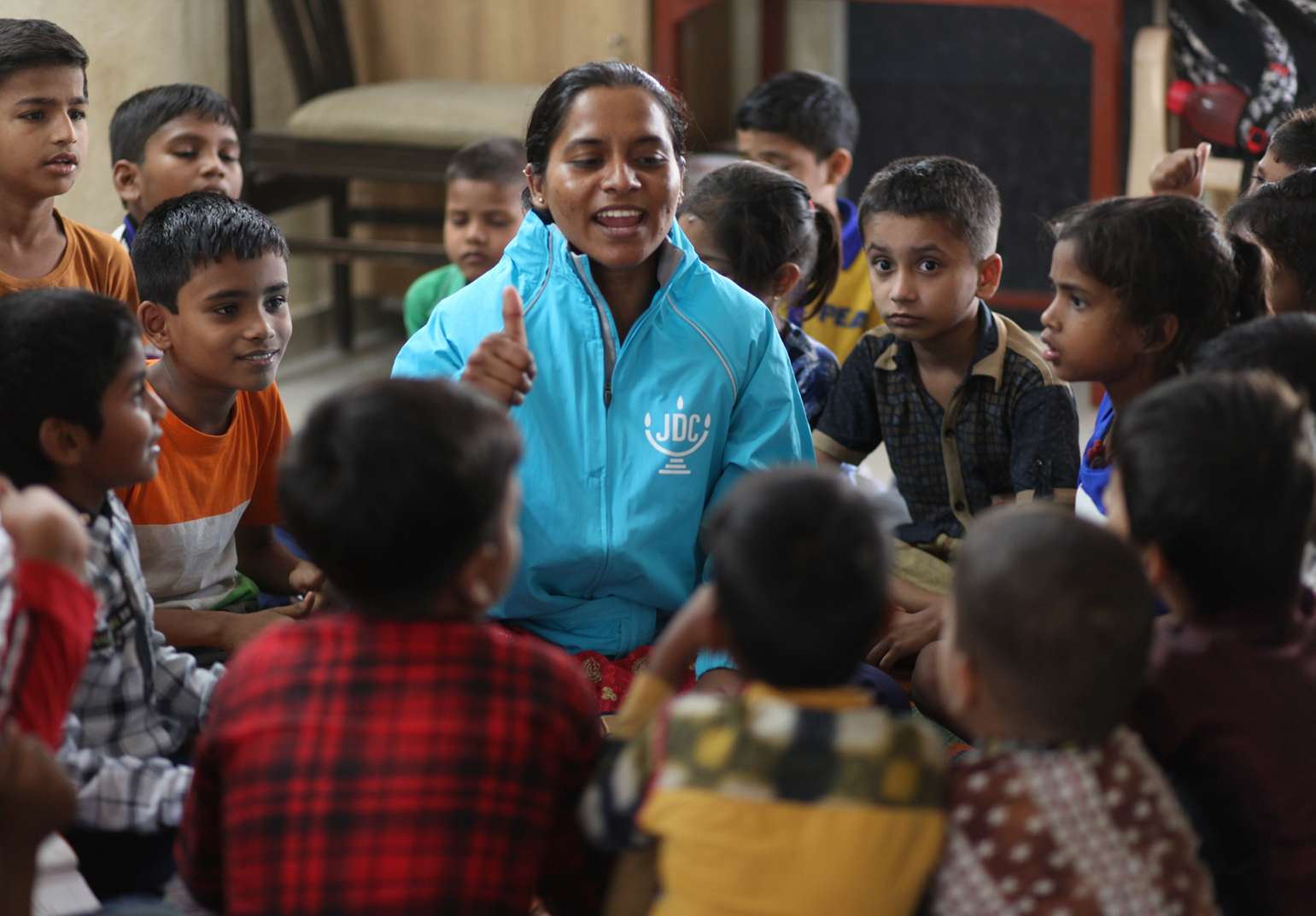 JDC Volunteer in India surrounded by group of young Indian boys smiles and raises her thumb.