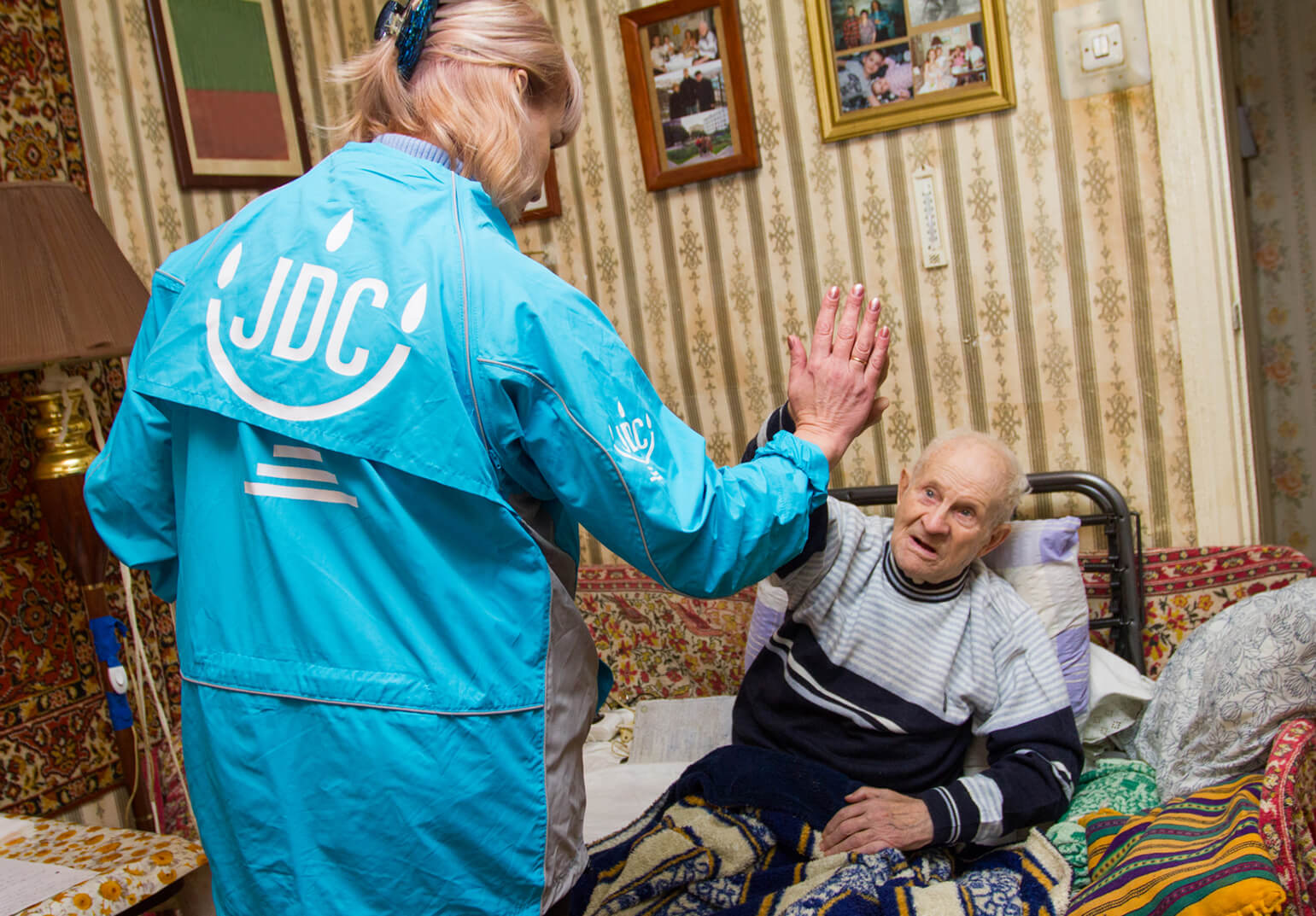 JDC homecare worker high-fiving an elderly male client in the former Soviet Union.