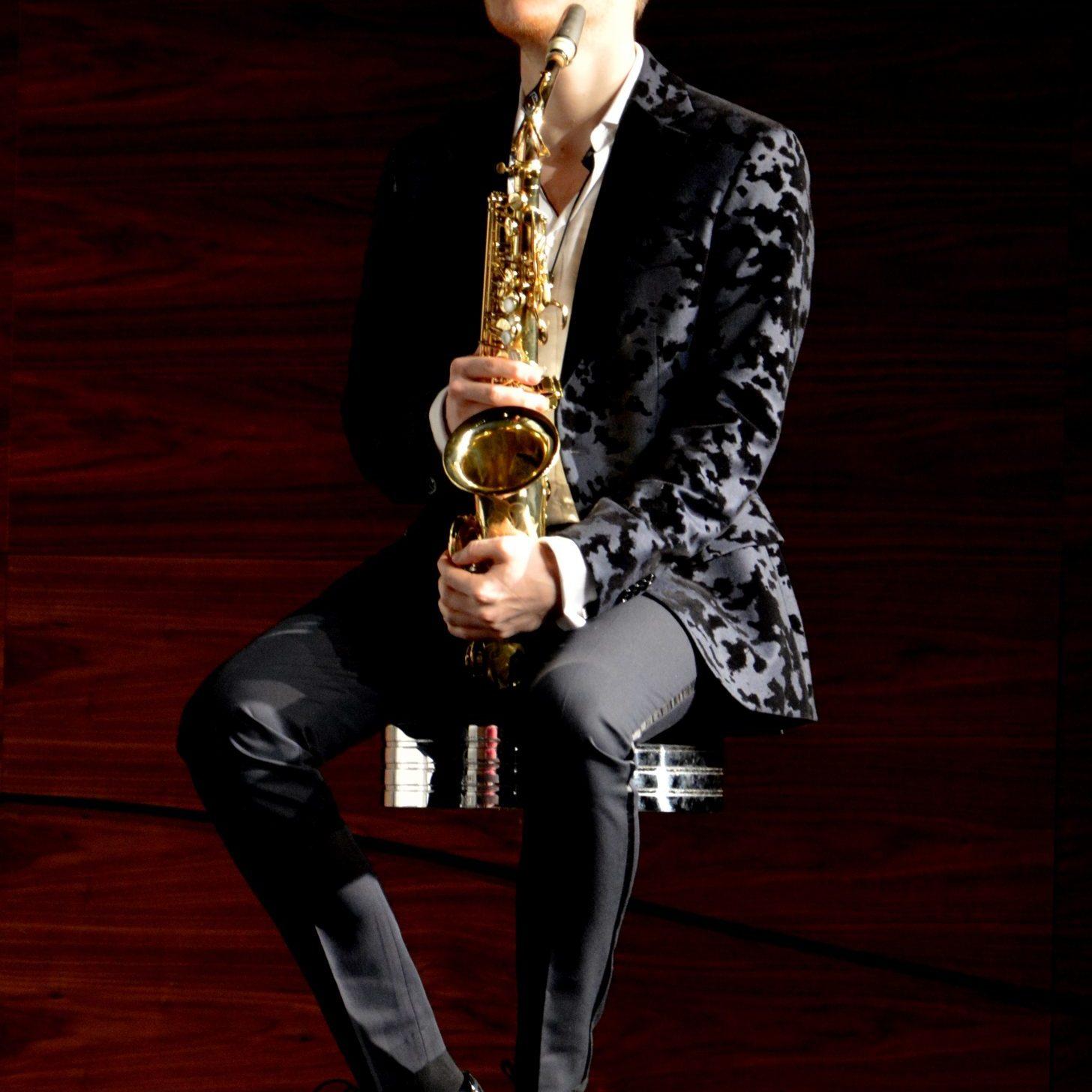Mężczyzna siedzi na krześle i trzyma saksofon