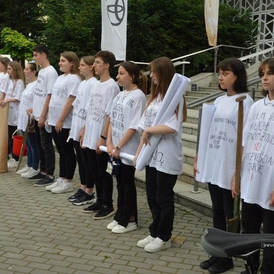 Przed schodami jasielskiego domu kultury stoi 14 młodych osób: chłopców i dziewcząt. Druga od prawej, ubrana w białą koszulkę trzyma łopatę, a od piąte do lewej -czerwone wiadro. Wszyscy ubrani w białe zapisane flamastrem koszulki oraz czarne spodnie. Przed nimi kamerzysta kręci ujęcia do filmu . Ubrany jest w szarą koszulkę, oliwkowe krótkie spodnie oraz oliwkowe sportowe buty