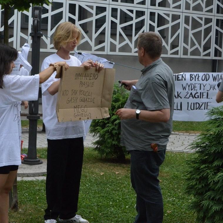 Na pierwszym planie reżyser tłumaczy młodemu aktorowi , co powinien zrobić. Młody chłopak, wysoko blondyn o półdługich włosach stoi z zapisanym kartonem , obok niego niska brunetka pomaga mu trzymać karton. Obydwoje ubrani są w białe koszulki i czarne spodnie. W tle kamerzysta filmuje wydarzenie