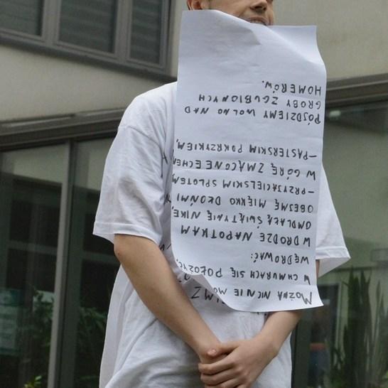 Młody chłopak stoi na murze, w ustach trzyma zapisaną do góry nogami kartkę papieru. Ma czarne włosy, białą koszulkę i czarne spodnie