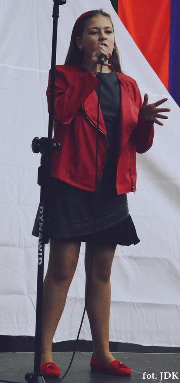 Nastoletnia dziewczyna ubrana w czerwoną kurtkę, czarna sukienkę i czerwone buty śpiewa na scenie plenerowej