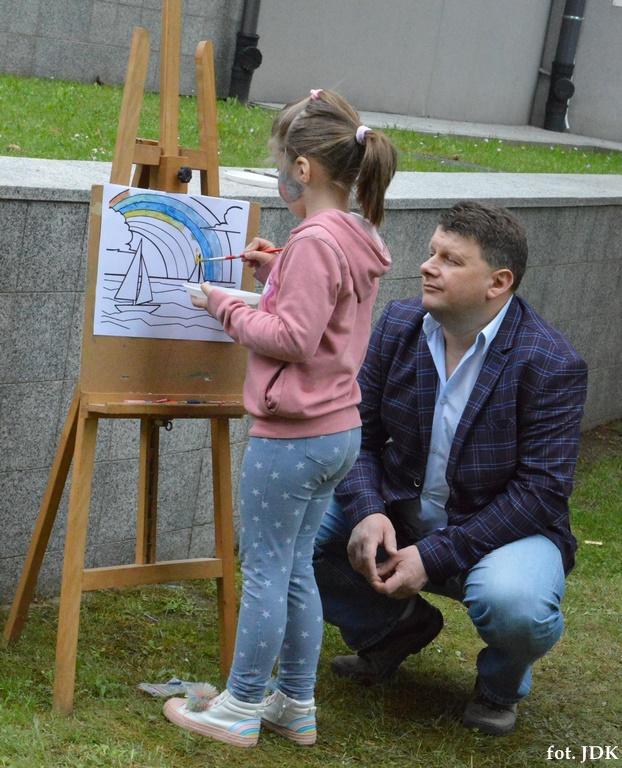 Dziecko maluje obrazek na sztaludze. Dziewczyna ubrana jest w różową bluzę, niebieskie leginsy w białe gwiazdki i biało różowe sportowe buty. Przy niej kuca mężczyzna w średnim wieku, ubrany w niebieską koszulę, marynarkę w granatowo-niebieską kratę oraz niebieskie dżinsy