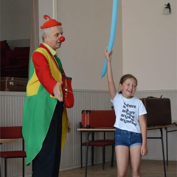 Klaun Feliks podarował dziewczynce z osiedla Hankówka balonowego pieska na smyczy z balonu.